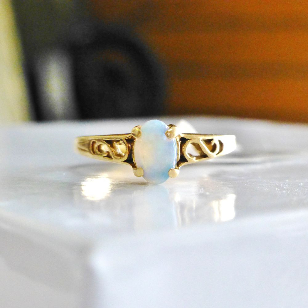 Oval cut fire opal prong set in a yellow gold scroll filigree ring