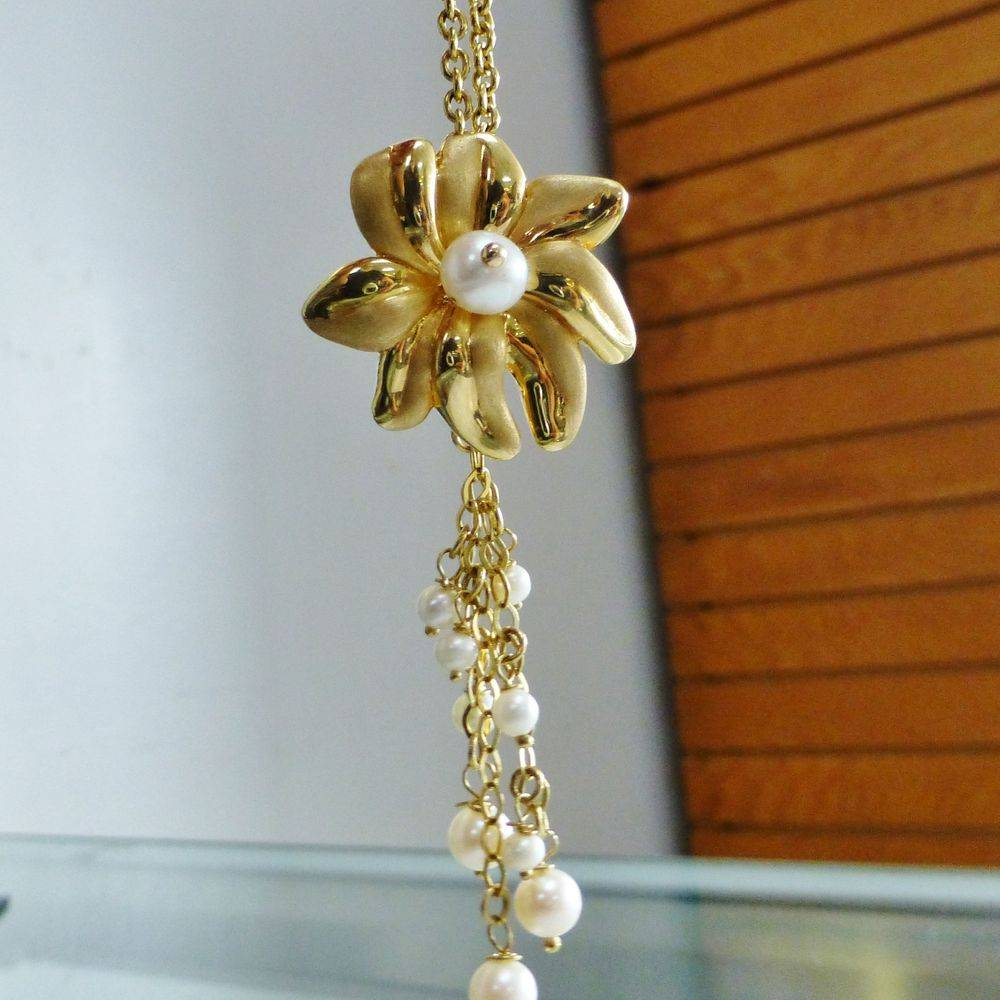 closeup picture of a yellow gold flower pendant with a cluster of dangling white pearls