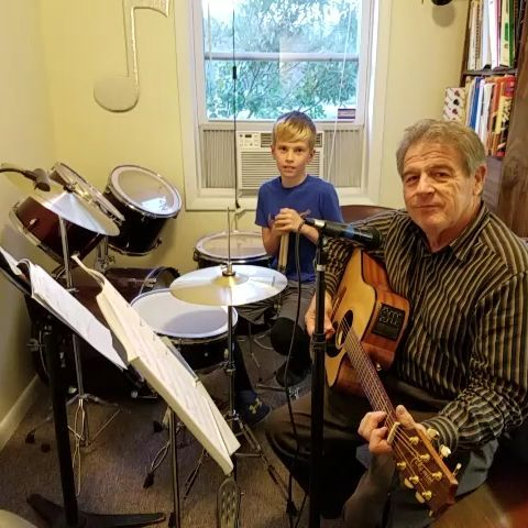 "Aidan R. (drum student) and Ray Braselton (drum teacher) play ""We Will Rock You""."