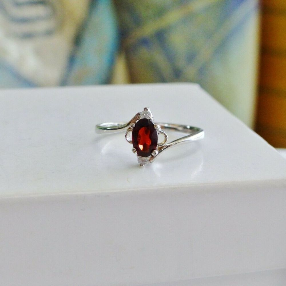 Ring with a deep red oval cut garnet solitaire with two diamond accents in white gold
