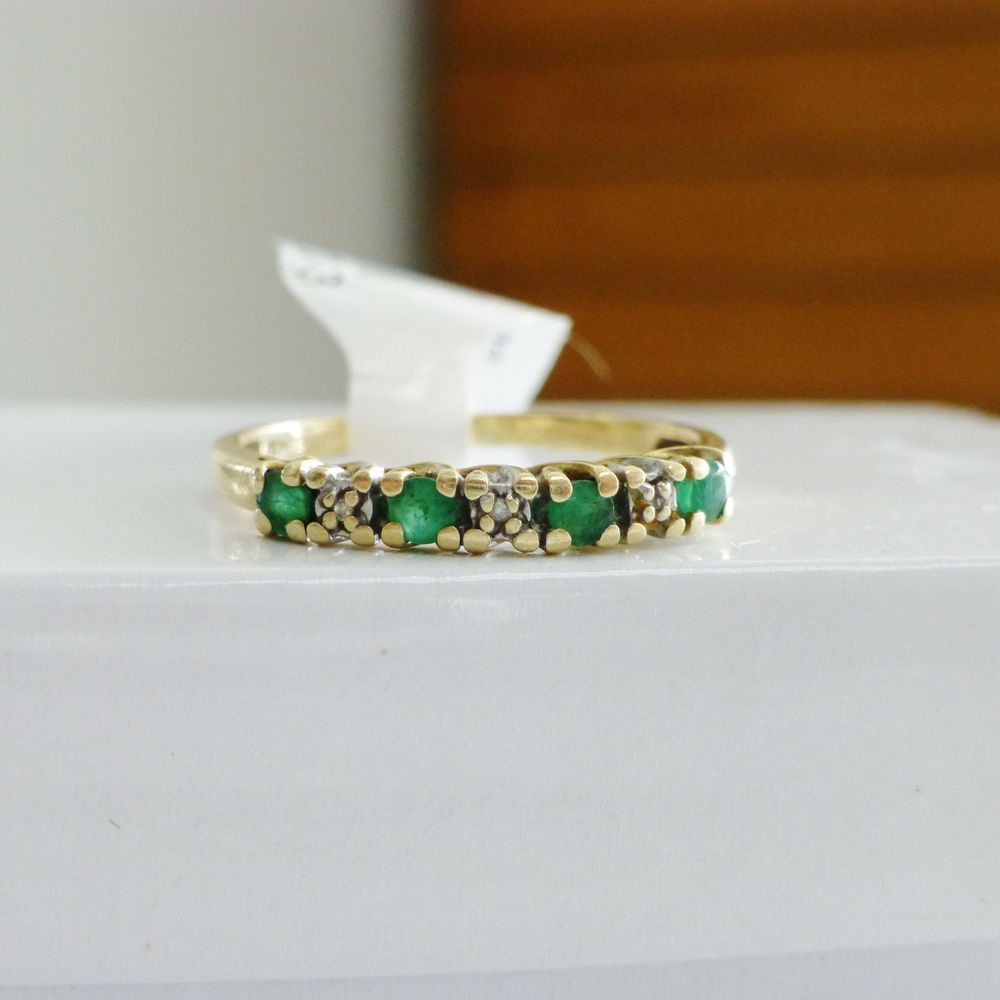 Closeup picture of a yellow gold band with alternating round green emerald and white diamonds