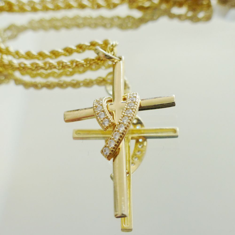 close up picture of a yellow gold rope chain with a round cut diamond wrap cross charm