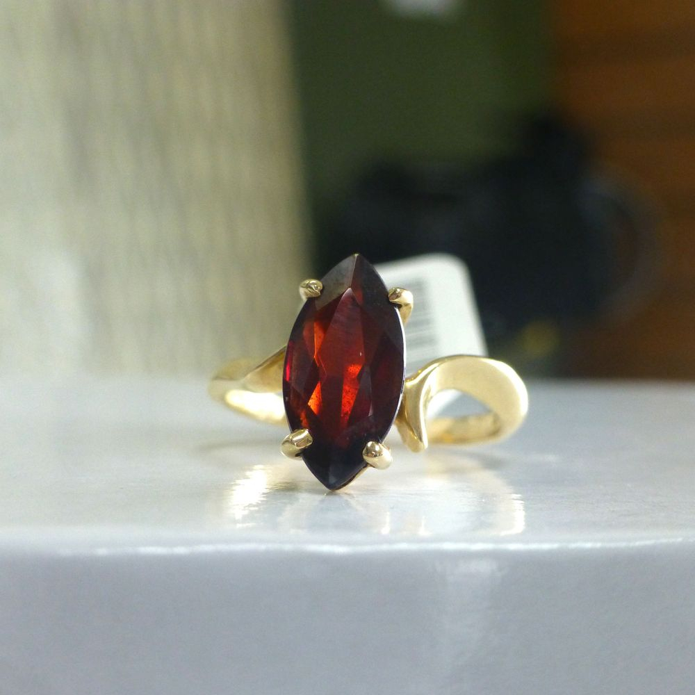 Marquise Cut Red Garnet Prong Set at the center of a yellow gold ring