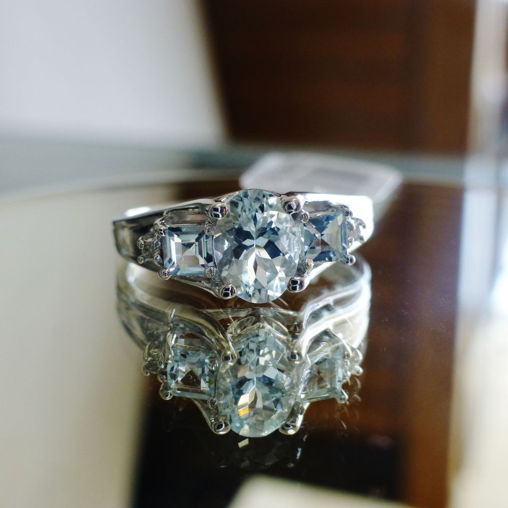 close up pihcture of a center oval cut aquamarine and two princess cut side stones prong set in a white gold ring