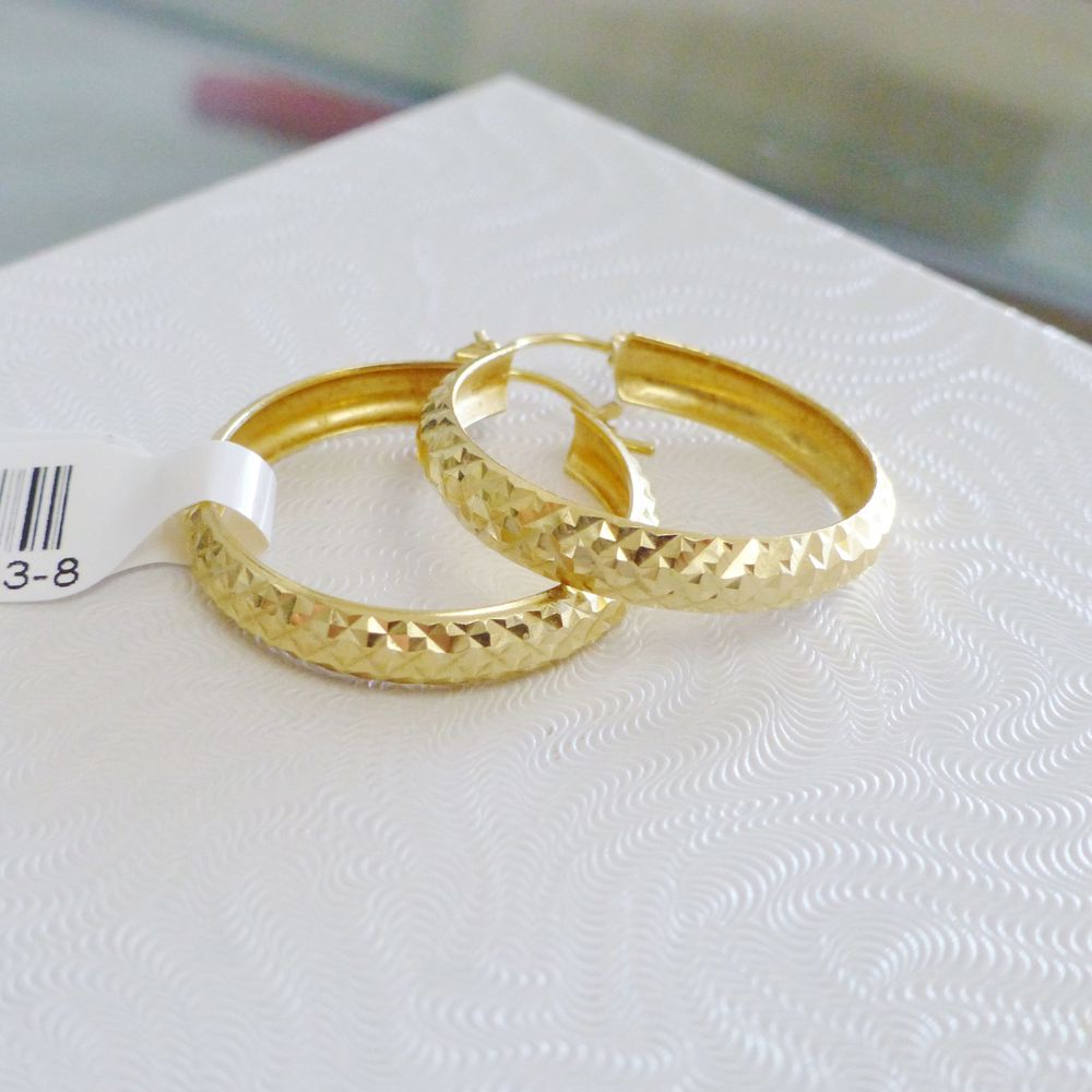 Close up picture of a pair of diamond cut hoop earrings