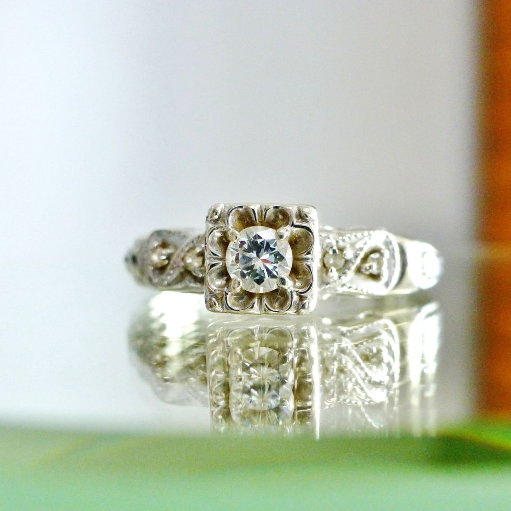 close up picture of an antique art deco white gold milgrain design engagement ring with a round cut diamond center stone