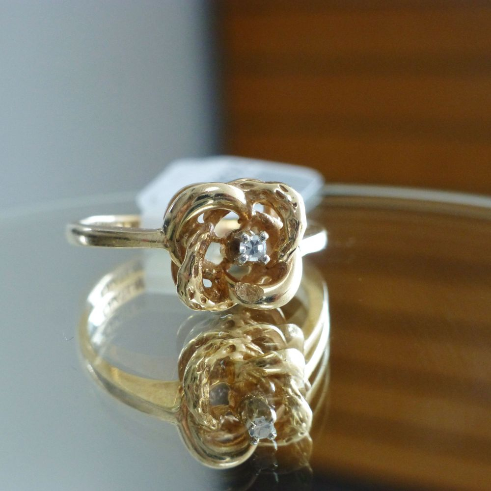 Close up picture of a diamond chip yellow gold love knot ring