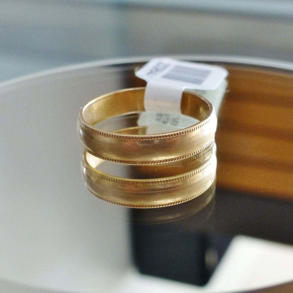 close up picture of a yellow gold ladies wedding band with milgrain design edges