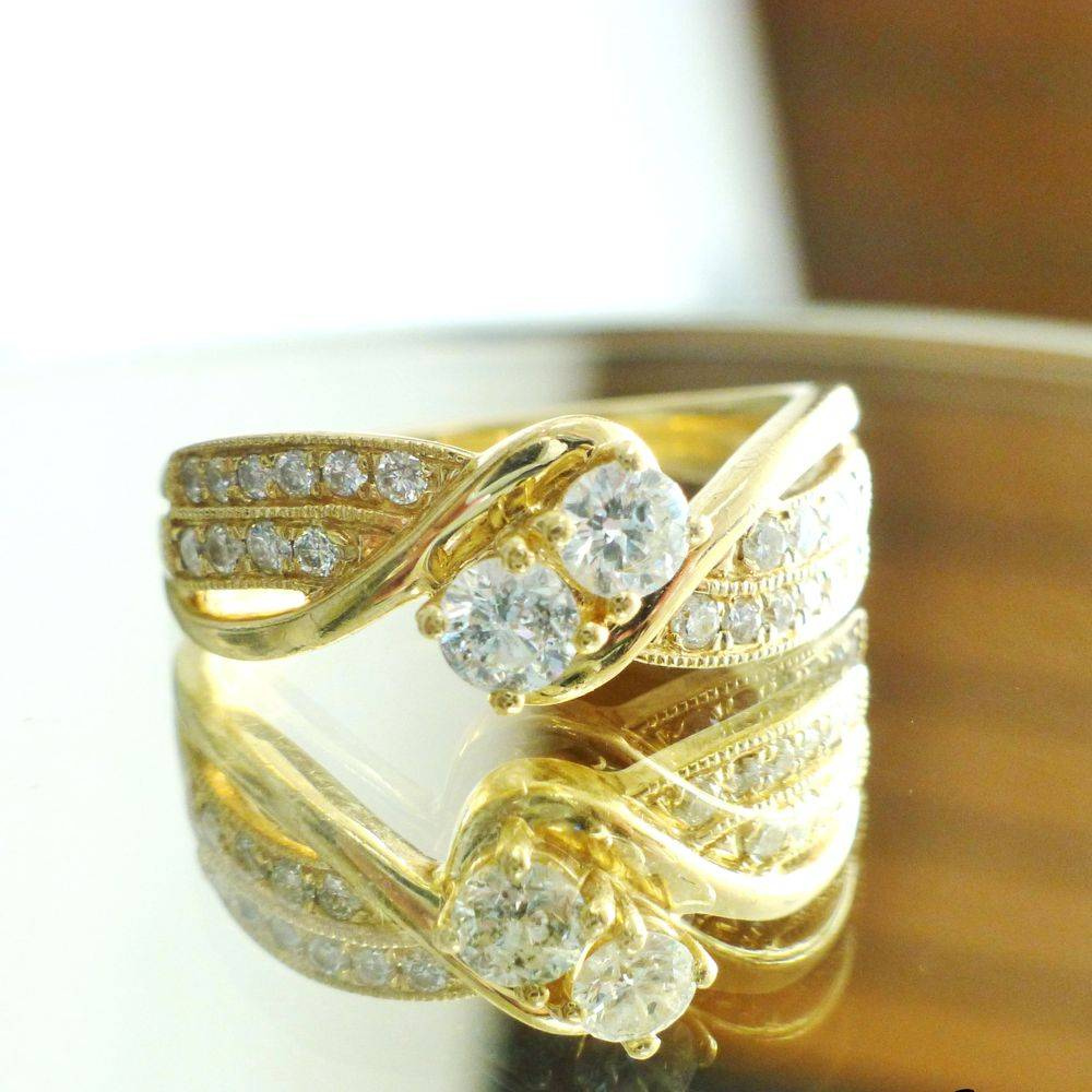 close up picture of a 14K yellow gold round cut diamond two stone bypass ring