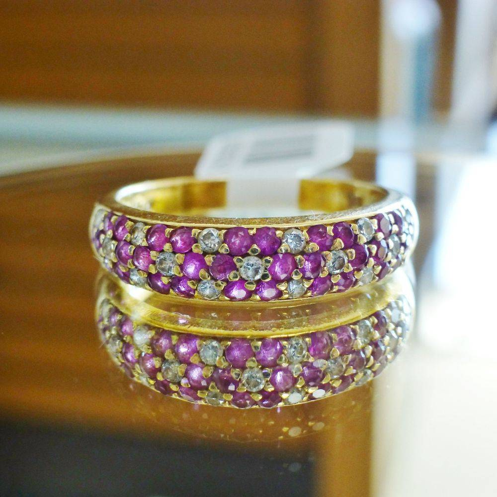 close up picture of a yellow gold Levian dome band with round ruby and diamond flowers