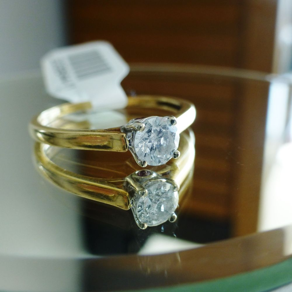 close up picture of a yellow gold engagement ring with a prong set, round cut diamond