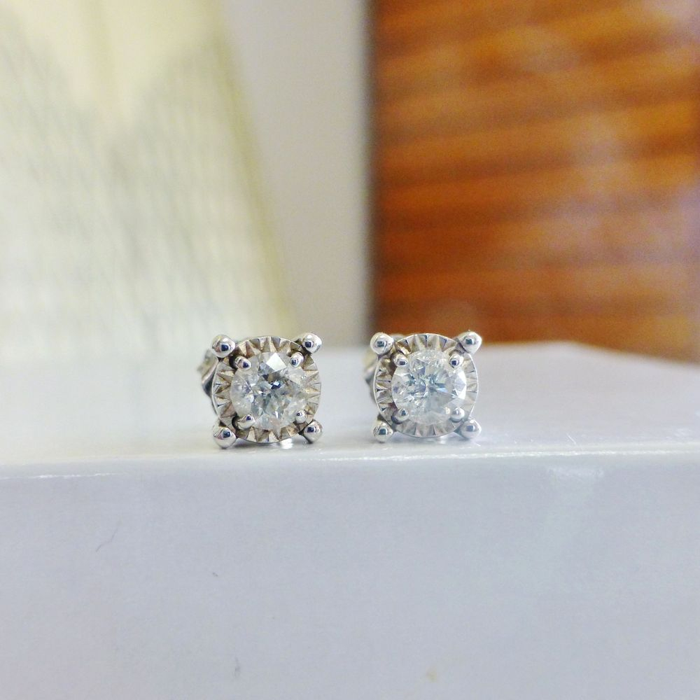 close up picture of white gold illusion set round cut diamond stud earring