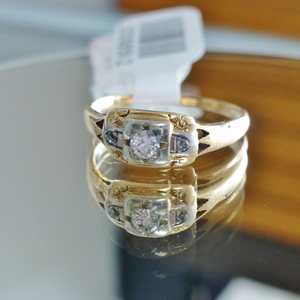 close up picture of a two tone gold art deco ring with three round cut diamonds