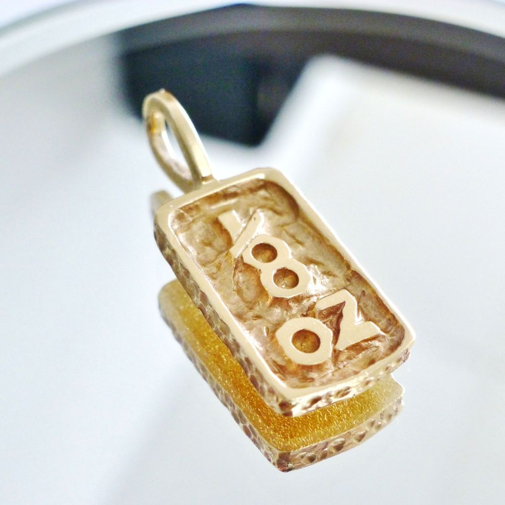 Close up picture of a yellow gold 1/8 oz rectangular nugget pendant