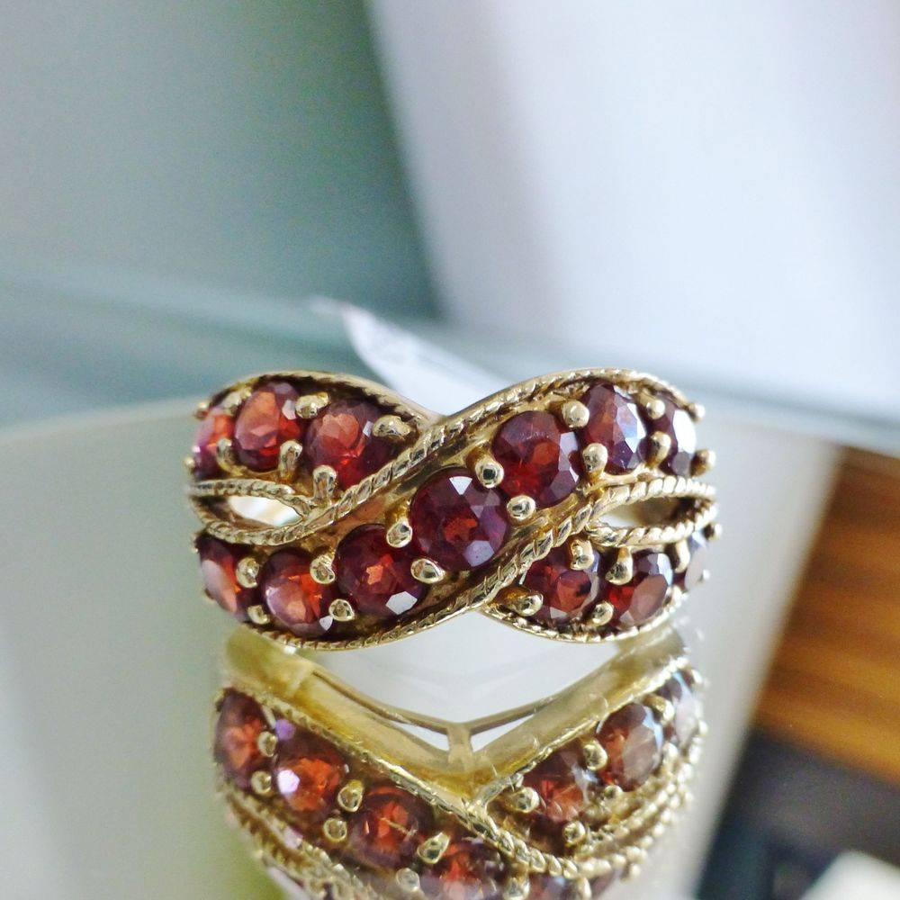 close up picture of a yellow gold milgrain edge criss cross band with round cut garnets