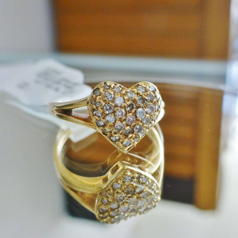 close up picture of a yellow gold heart ring filled with prong set round diamonds