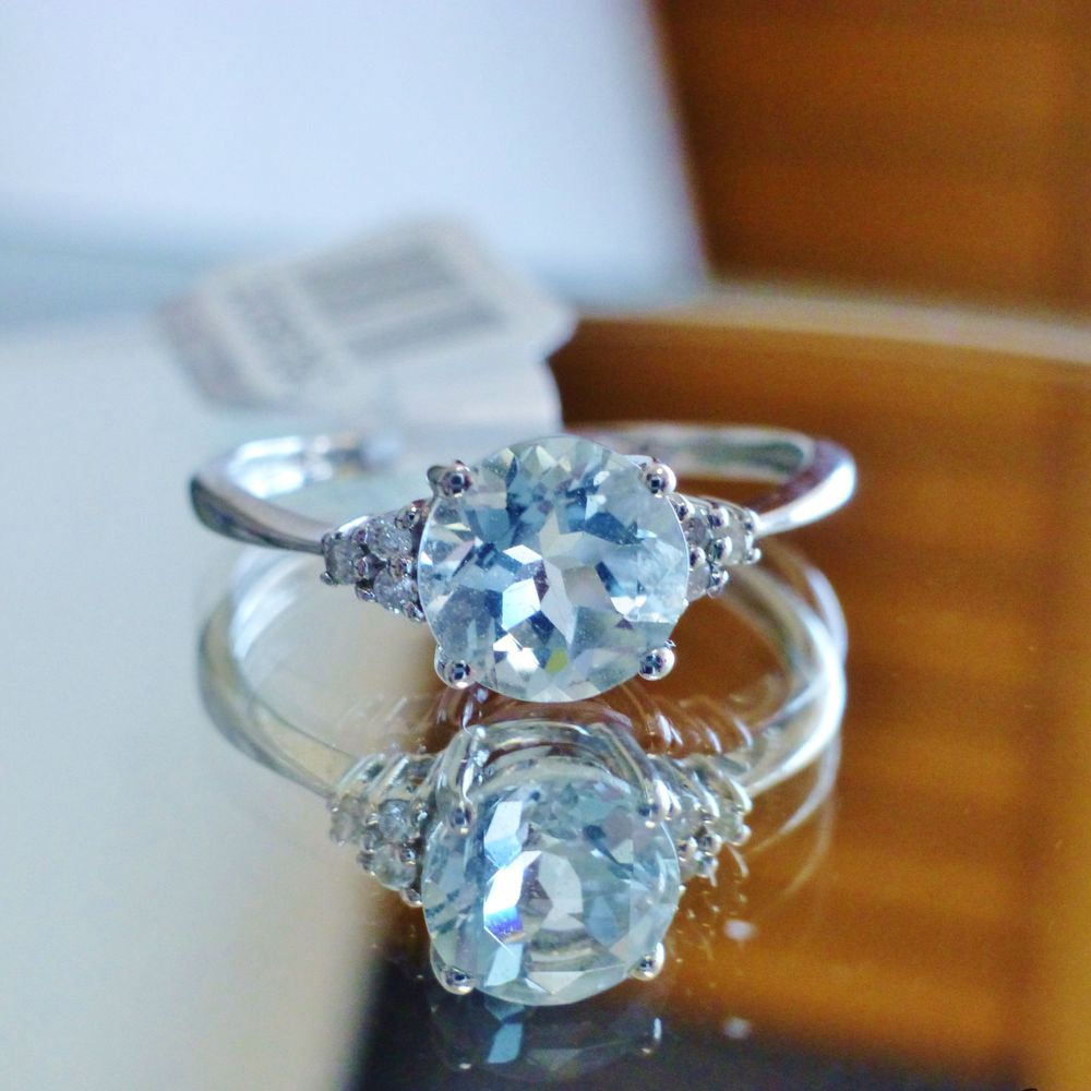close up picture of a round cut aquamarine diamond accent ring in white gold