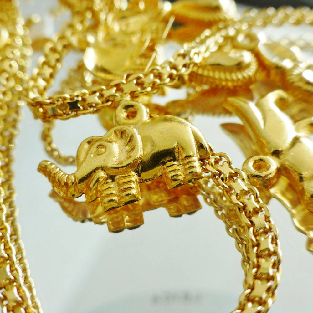 yellow gold ankle bracelet with dangling elephant, hearts and tiger charms