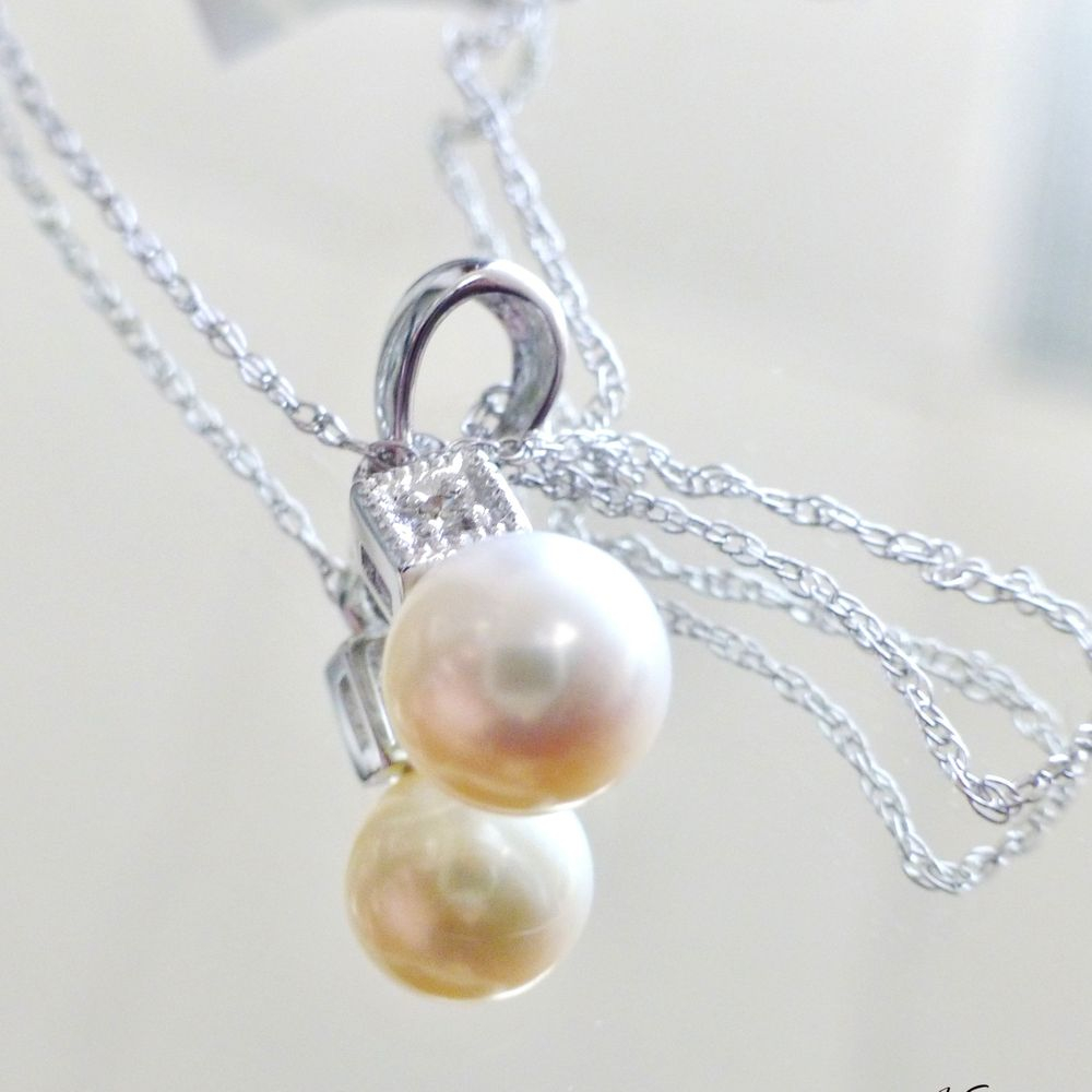 close up picture of a round pearl and diamond pendant on a white gold cable link necklace