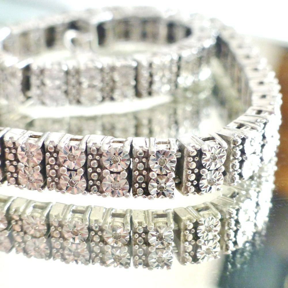 close up picture of a double row of illusion set diamonds in a sterling silver tennis bracelet