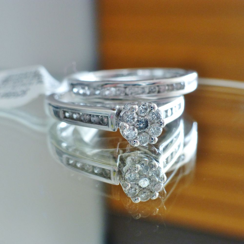 picture of a white gold round diamond flower bridal two ring set