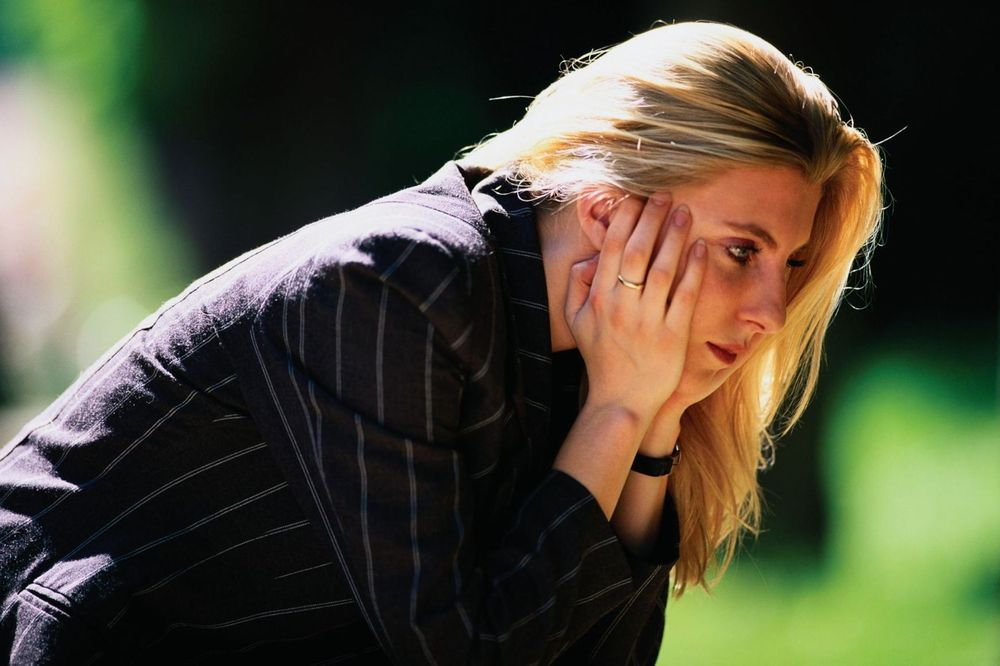 image of a depressed woman sitting outside holding face in her hands