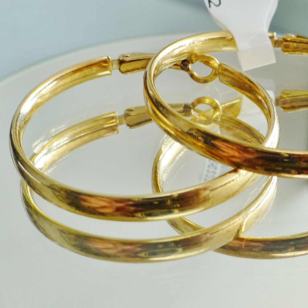 closeup picture of a pair of gold tone sterling silver hoop earrings