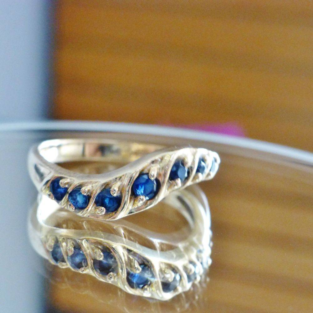 upclose picture of a yellow gold wavy stackable ring with round cut blue sapphires
