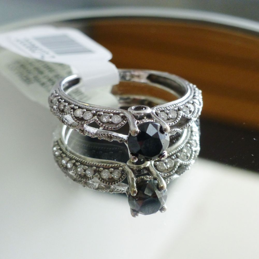 upclose picture of a white gold round black and white diamond scallop edge ring