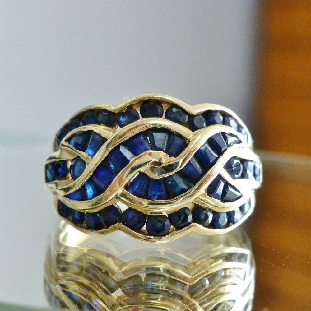 Closeup picture of a yellow gold round and baguette blue sapphire swirl ring