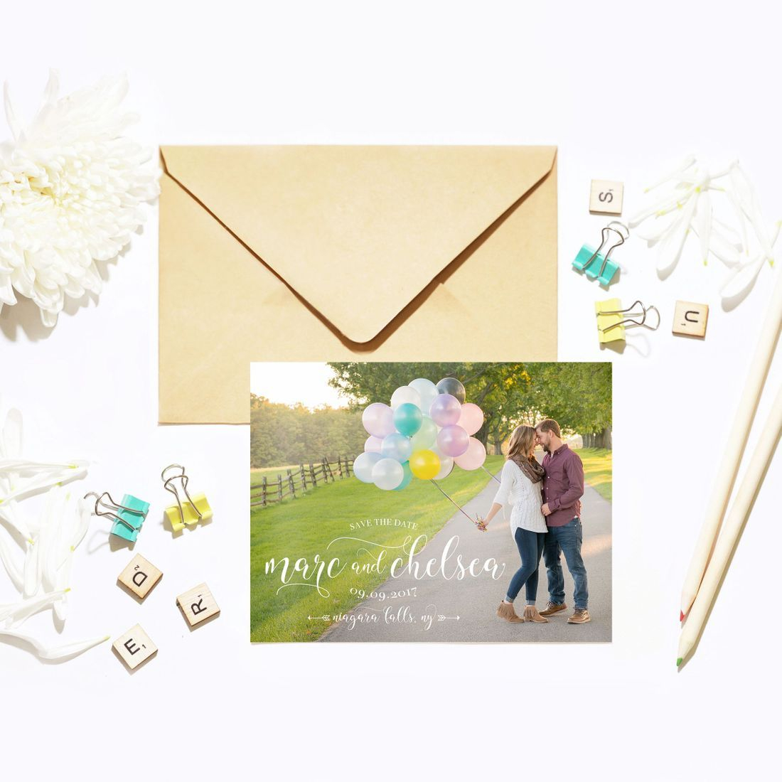 Save the date flat lay of engaged couple with balloons on country lane