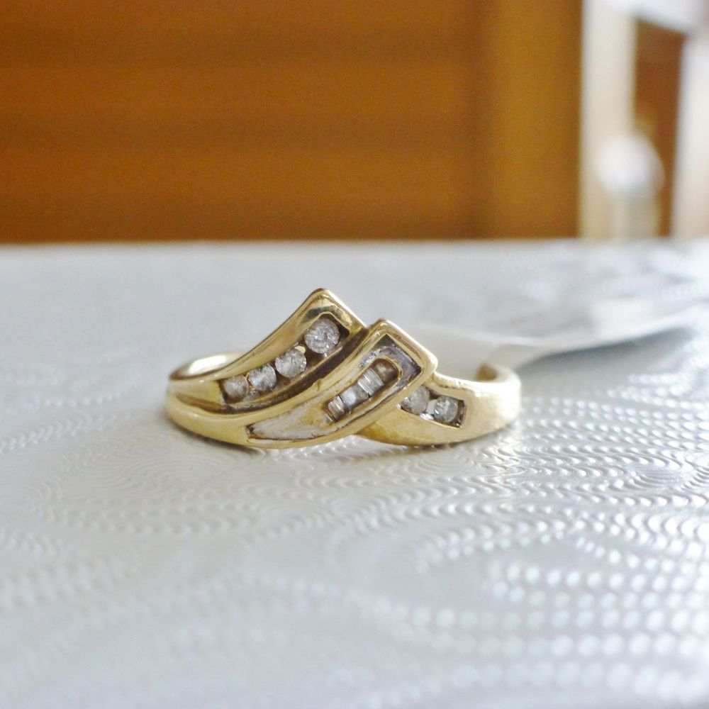 close up picture of a yellow gold chevron style ring with round and baguette diamonds