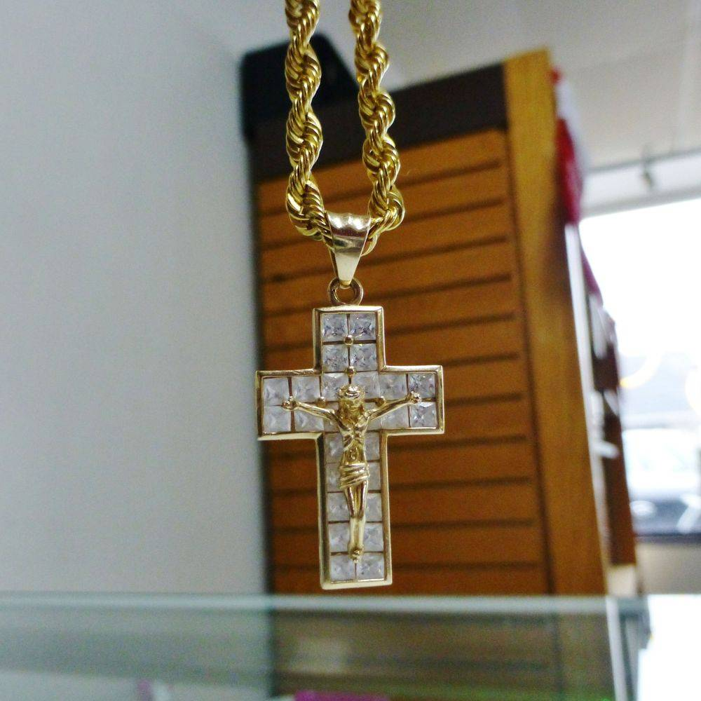 Closeup Picture of a yellow gold crucific cross pendant on a rope chain with cubic zirconia