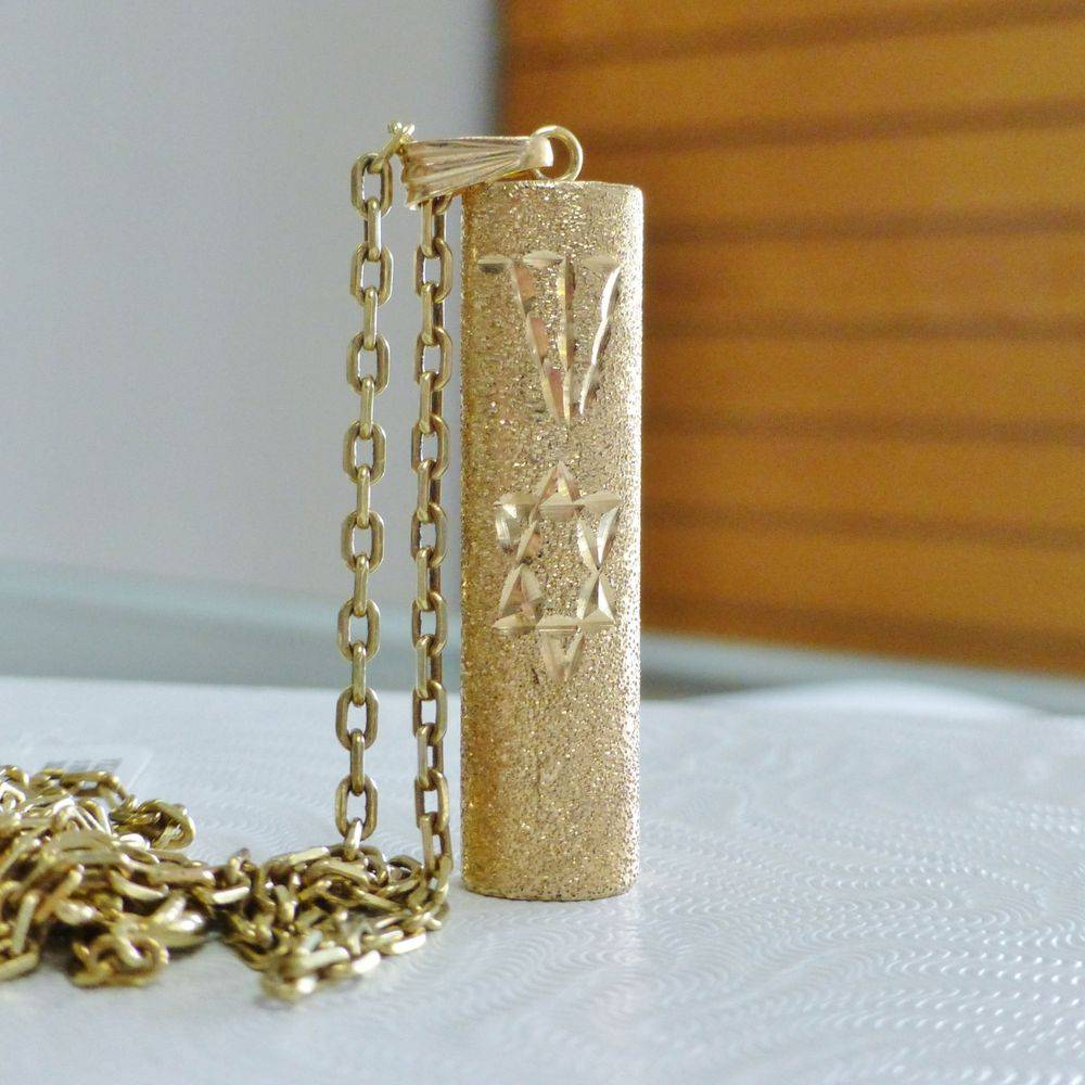 close up picture of a yellow gold cable link chain with a star of David tube pendant