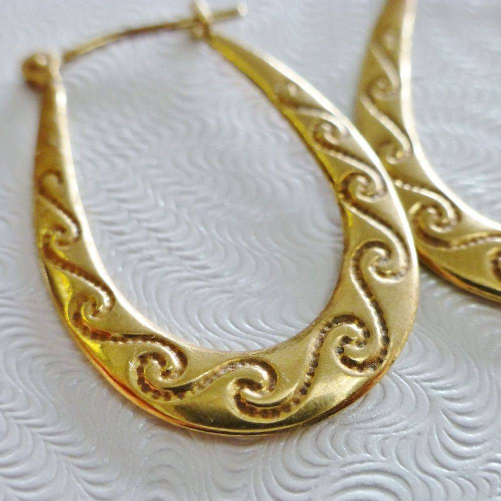 closeup picture of a flat yellow gold hoop earring with an etched wave design