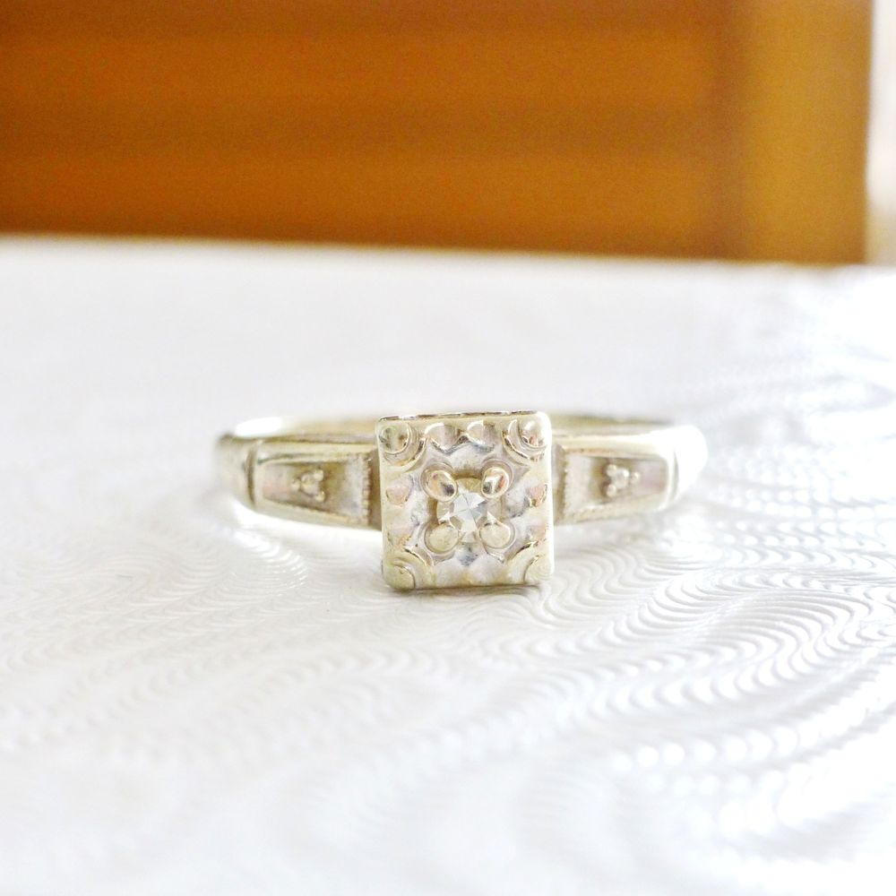 Close up picture of a white gold mid century engagement ring