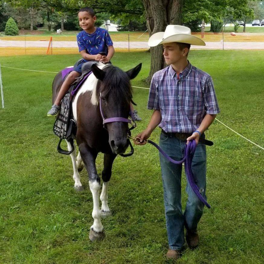 Boy riding a pony led by a cowboy