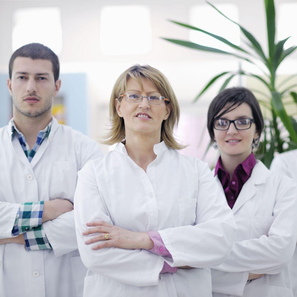 three dentists smiling at the camera