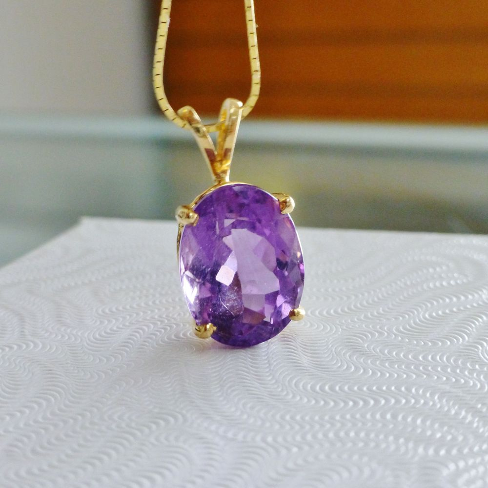 closeup picture of an oval cut purple amethyst prong set in yellow gold