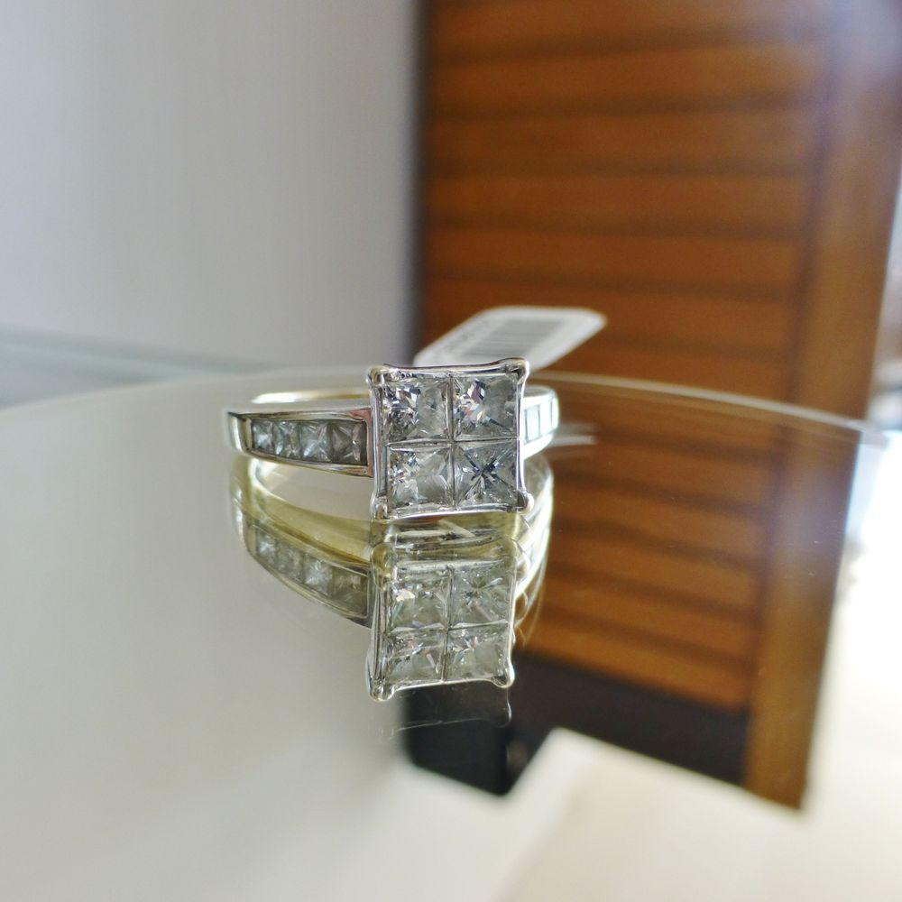 Close up picture of a princess cut diamond quad engagement ring in white gold