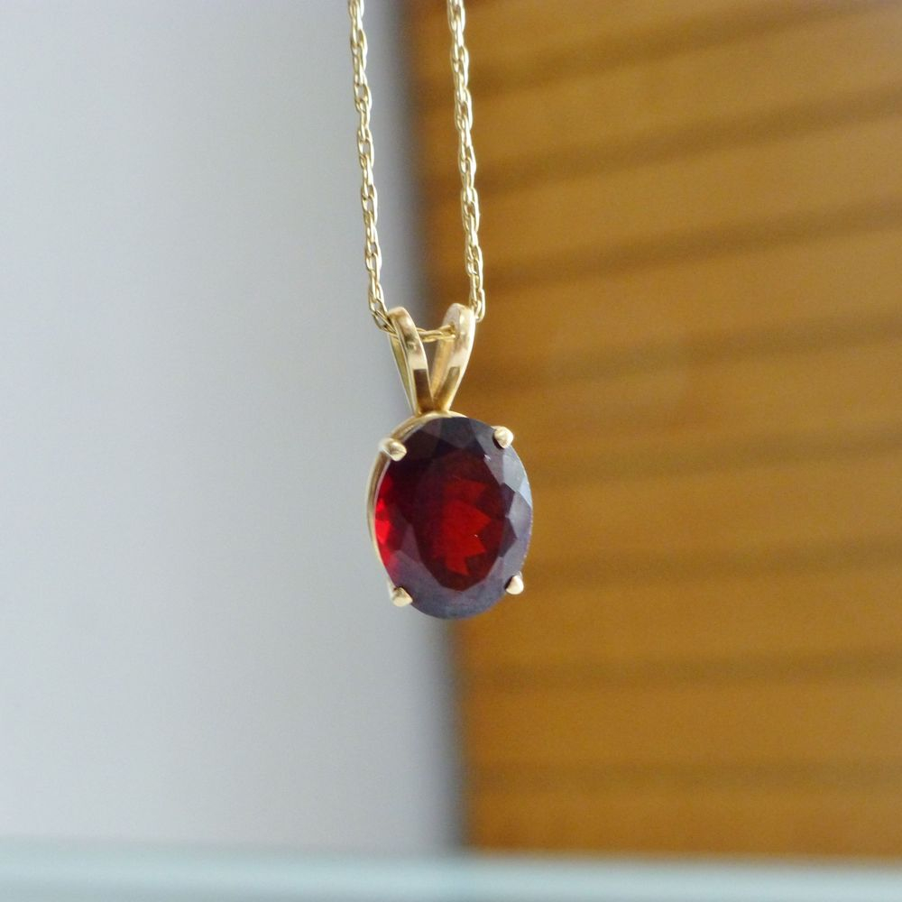 close up picture of a yellow gold cable link chain with an oval cut prong set red garnet charm