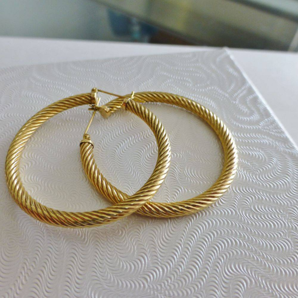 closeup picture of a pair of yellow gold twisted hoop earrings