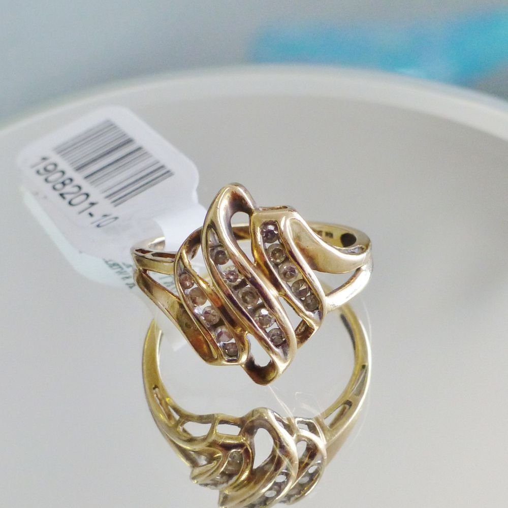 closeup picture of a yellow gold swirling channel set round cut diamond cluster ring