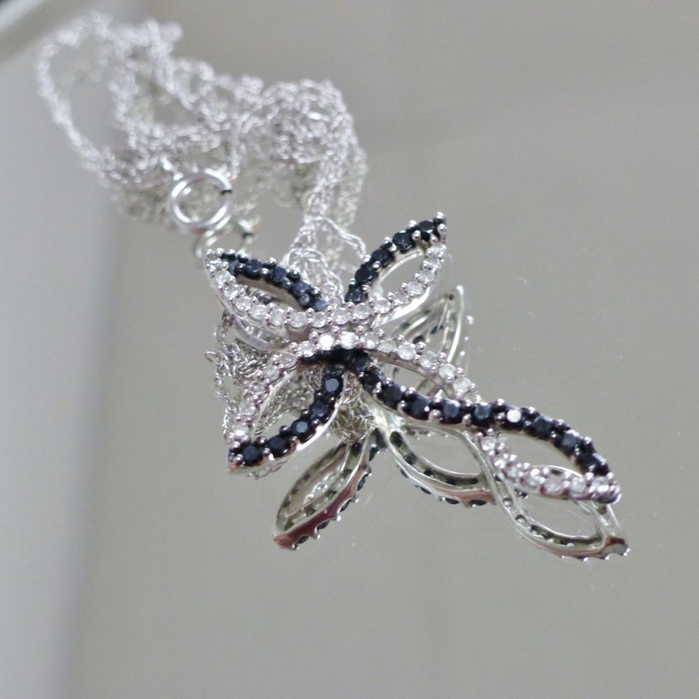 closeup picture of a white gold black and white diamond twist ribbon cross charm on chain