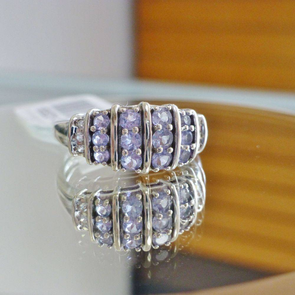 Closeup picture of round cut tanzanite and diamond accent white gold dome style ring
