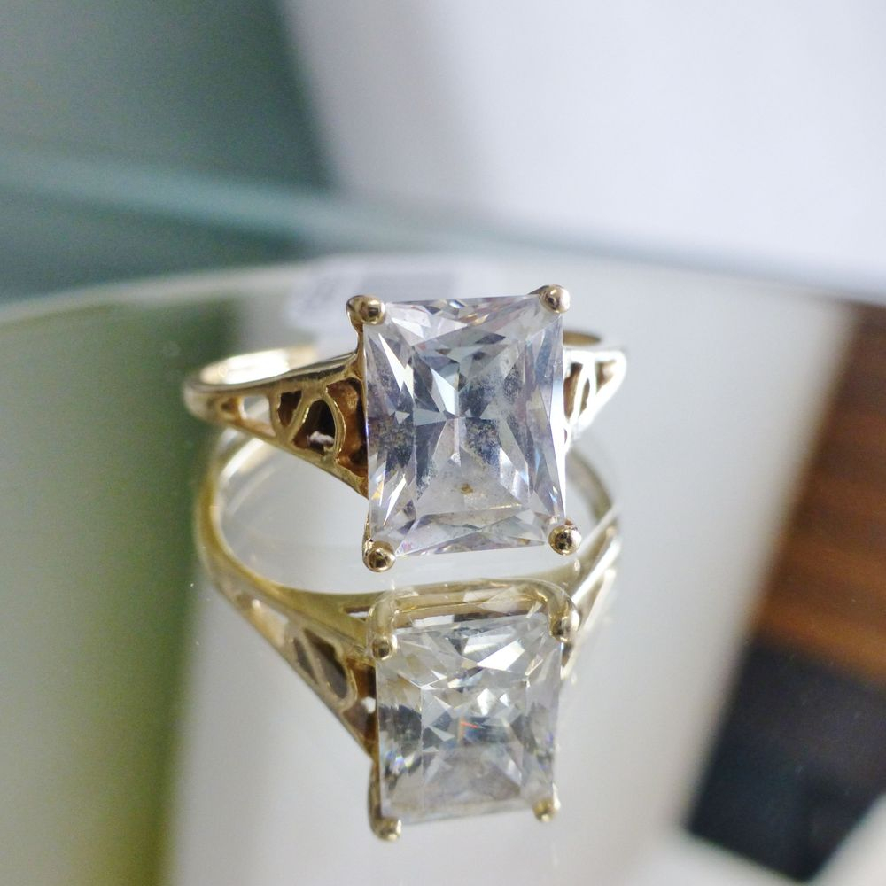 close up picture of a yellow gold filigree ring with an emerald cut diamond simulant prong set and centered