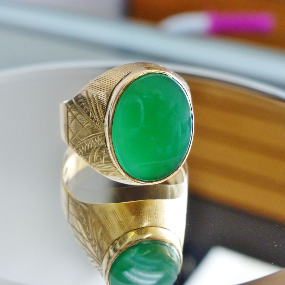 Closeup picture of a yellow gold textured ring with an oval cut bezel set green agate stone