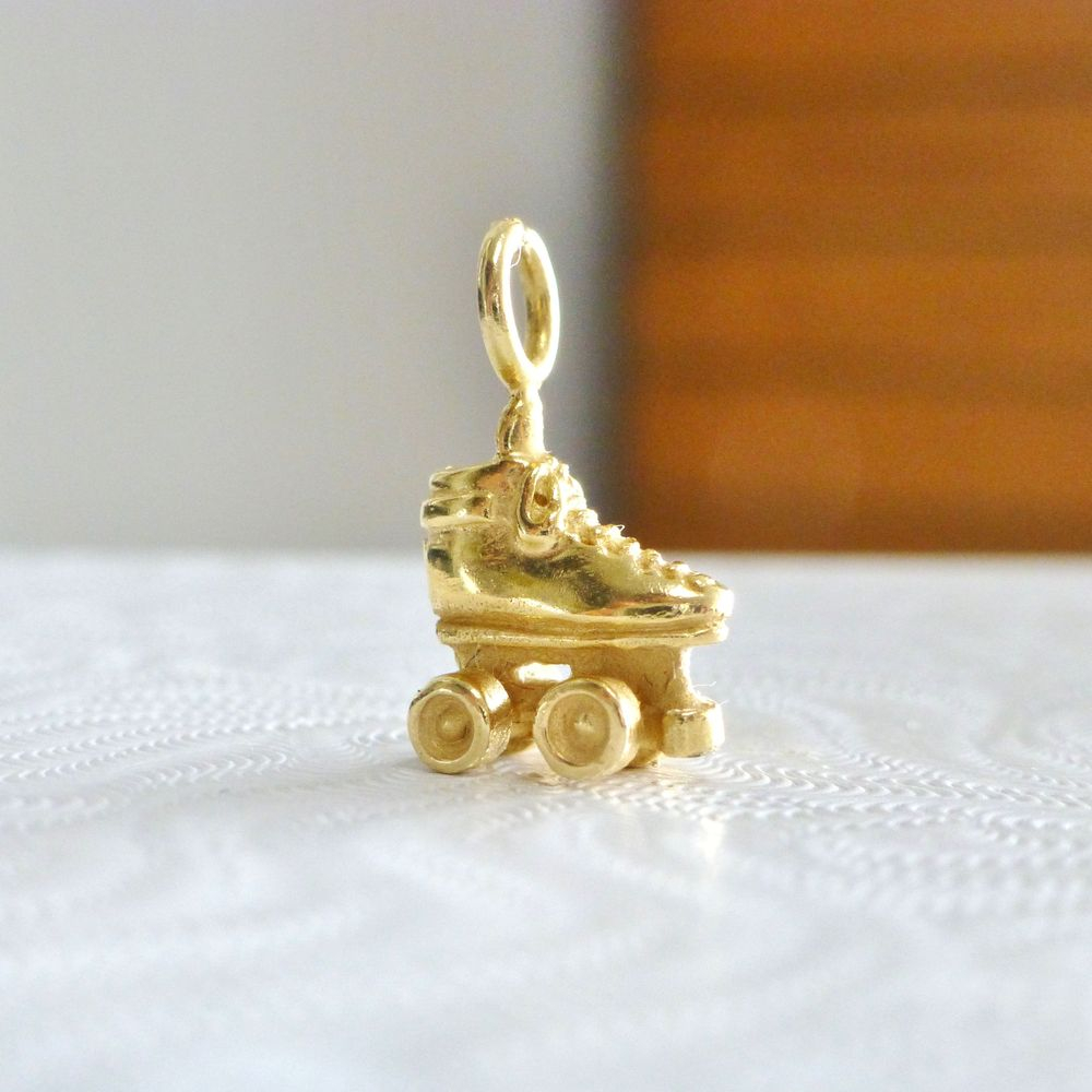 close up picture of a yellow gold 3D roller skate pendant on a white box