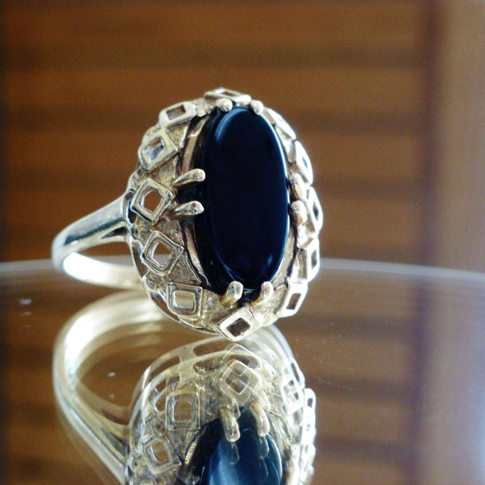 closeup picture of an open work gold framed oval black onyx cocktail ring