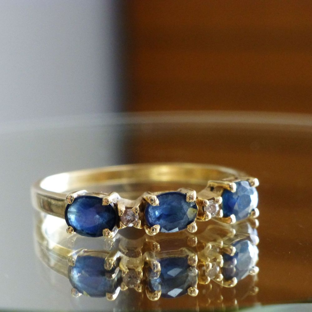closeup picture of a yellow gold band with alternating oval cut blue sapphires and round cut diamond accents